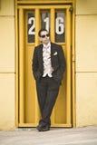 Hombre hermoso que se inclina contra el marco de puerta amarillo que lleva el traje elegante Fotos de archivo