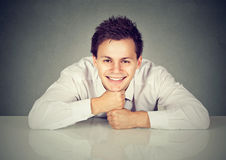 Hombre hermoso que se inclina en la tabla blanca y que sonríe en la cámara Fotografía de archivo libre de regalías