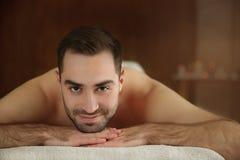Hombre hermoso que se relaja en la tabla del masaje fotos de archivo