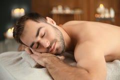 Hombre hermoso que se relaja en la tabla del masaje fotografía de archivo libre de regalías