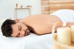 Hombre hermoso que se relaja en la tabla del masaje imágenes de archivo libres de regalías