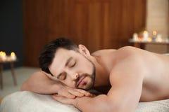 Hombre hermoso que se relaja en la tabla del masaje imagen de archivo