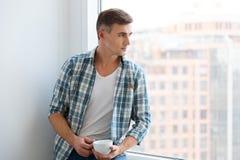 Hombre hermoso que se sienta en alféizar y el café de consumición Fotografía de archivo libre de regalías