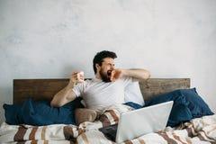 Hombre hermoso que se sienta en cama y estirar imagenes de archivo