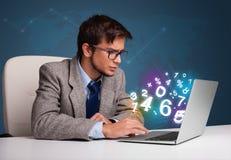 Hombre hermoso que se sienta en el escritorio y que pulsa en la computadora portátil con el número 3d Foto de archivo