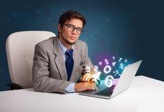 Hombre hermoso que se sienta en el escritorio y que pulsa en la computadora portátil con el número 3d Imagen de archivo libre de regalías