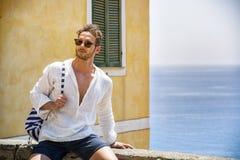 Hombre hermoso que se sienta en la ciudad de la playa imagenes de archivo
