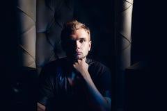 Hombre hermoso que se sienta en la silla en la sombra Fotos de archivo libres de regalías