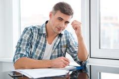 Hombre hermoso que se sienta en la tabla y la escritura Imagen de archivo libre de regalías