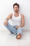 Hombre hermoso que se sienta en suelo por la pared Imágenes de archivo libres de regalías