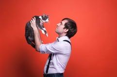 Hombre hermoso que se sostiene en los brazos extendidos y que mira el gato gris y blanco lindo imagenes de archivo