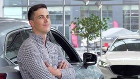 Hombre hermoso que sonríe soñador, inclinándose en un nuevo coche en la representación almacen de video