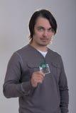 Hombre hermoso que sostiene el preservativo verde Imagen de archivo libre de regalías
