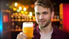 Hombre hermoso que sostiene el vidrio de cerveza fresca, pasando tiempo en la cervecería, prueba de la cerveza fotografía de archivo