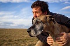 Hombre hermoso que sostiene su perro que mira en el viento Fotos de archivo