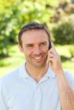 Hombre hermoso que telefona en el parque Fotos de archivo