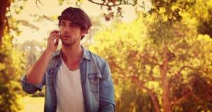Hombre hermoso que tiene una llamada de teléfono en el parque almacen de metraje de vídeo