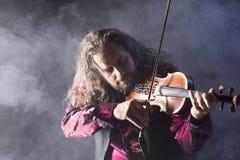 Hombre hermoso que toca el violín clásico en humo azul Imágenes de archivo libres de regalías