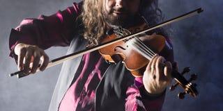 Hombre hermoso que toca el violín clásico en humo azul Foto de archivo