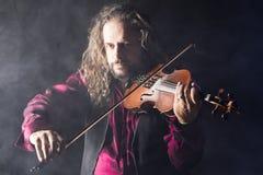 Hombre hermoso que toca el violín clásico en humo azul Fotos de archivo libres de regalías