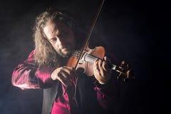 Hombre hermoso que toca el violín clásico en humo azul Foto de archivo libre de regalías