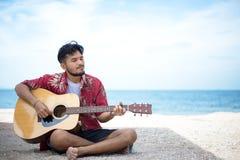Hombre hermoso que toca la guitarra clásica que se sienta en la playa Fotografía de archivo