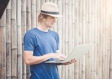 Hombre hermoso que trabaja con el ordenador portátil en la pared de bambú Fotos de archivo libres de regalías