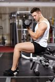 Hombre hermoso que trabaja con pesas de gimnasia pesadas en el gimnasio Foto de archivo