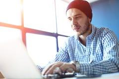 Hombre hermoso que trabaja de su Ministerio del Interior Analice los planes empresariales en el ordenador portátil Fondo borroso, imagenes de archivo