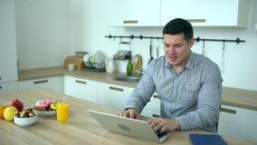 Hombre hermoso que trabaja en el ordenador portátil en casa A cámara lenta El hombre de negocios joven trabaja de hogar usando el almacen de video