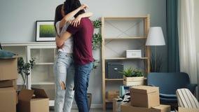 Hombre hermoso que trae a la esposa a la nueva casa que hace girar y que se besa expresando amor almacen de video