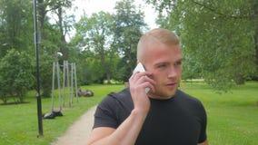 Hombre hermoso que usa un teléfono móvil en un parque durante día de verano almacen de metraje de vídeo
