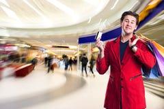 Hombre hermoso sonriente con los panieres y la tarjeta de crédito Foto de archivo libre de regalías
