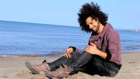 Hombre hermoso sonriente feliz que se sienta en la playa almacen de video