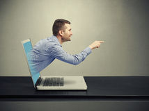 Hombre hermoso sonriente salido del ordenador portátil Fotografía de archivo