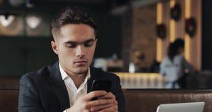 Hombre hermoso usando el smartphone que se sienta en café u oficina coworking Retrato del empresario acertado del hombre de negoc almacen de metraje de vídeo