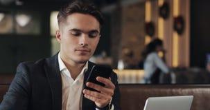 Hombre hermoso usando el smartphone que se sienta en café u oficina coworking Retrato del empresario acertado del hombre de negoc metrajes