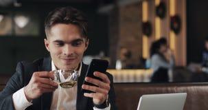 Hombre hermoso usando el smartphone y el té de consumición que se sientan en café u oficina coworking Retrato del hombre de negoc almacen de video