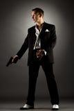 Hombre hermoso vestido como gángster que sostiene el arma Foto de archivo libre de regalías