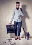 Hombre hermoso y gato que escuchan la música en un magnetophone Imágenes de archivo libres de regalías