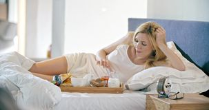 Hombre hermoso y mujer que comen el desayuno con los bollos de leche en cama Los pares por mañana del amor despiertan en casa en  almacen de video