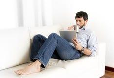 Hombre hispánico atractivo joven en casa en el sofá blanco usando la tableta o el cojín digital Imagenes de archivo