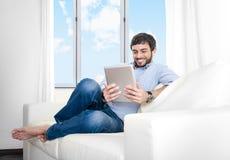 Hombre hispánico atractivo joven en casa que se sienta en el sofá blanco usando la tableta digital Fotografía de archivo libre de regalías