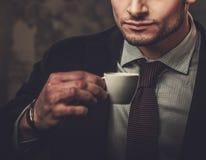 Hombre hispánico bien vestido serio con la taza de presentación del café Fotos de archivo