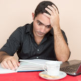 Hombre hispánico cansado que estudia en casa Foto de archivo libre de regalías
