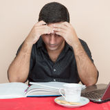 Hombre hispánico cansado que estudia en casa Imágenes de archivo libres de regalías