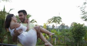Hombre hispánico Carry Woman Outdoors On Terrace, par feliz en amor hablando sobre puesta del sol en bosque tropical almacen de video