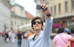 Hombre hispánico del inconformista de moda joven con las gafas de sol que toman un selfie Fotos de archivo libres de regalías
