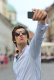 Hombre hispánico del inconformista de moda joven con las gafas de sol que toman un selfie Imagenes de archivo