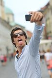 Hombre hispánico del inconformista de moda joven con las gafas de sol que toman un selfie Foto de archivo